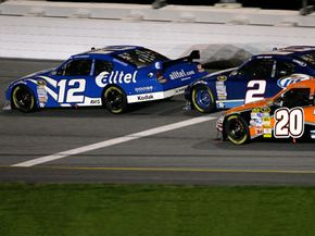 NASCAR driver Ryan Newman (12) passes Tony Stewart (20) on the backstretch as he gets drafting help from Kurt Busch (2) on the final lap of the 50th running of the Daytona 500 at Daytona International Speedway. Newman won the race.