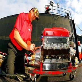 A crew member prepares an engine for a NASCAR race.