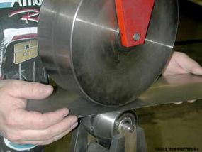 An English wheel is used to shape the flat sheet metal into curved body panels.