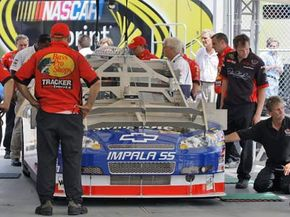 NASCAR officials inspect Martin Truex Jr.'s car as some of his crew members look on, July 3, 2008, at Daytona International Speedway in Daytona Beach, Fla. The car was impounded.