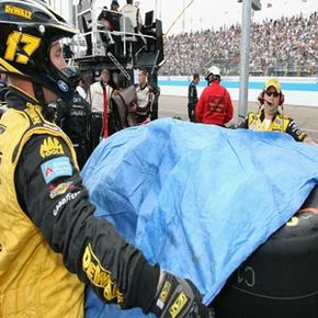Crew members cover up tires during a NASCAR rain delay. Rain poses several major safety risks to drivers.