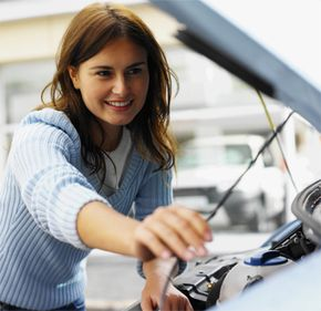 A woman checks the oil level of her car with the dipstick.