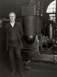 Thomas A. Edison stands next to his original electric dynamo.