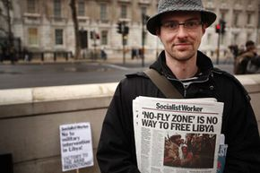 A man sells copies of The Socialist Worker newspaper in London, as demonstrators protest against British involvement in a no-fly operation over Libya in 2011.
