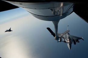 """A French air force fighter jet refuels with a Boeing refueling tanker over the Mediterranean sea during the no-fly zone operation """"Harmattan"""" in the critical region on Benghazi, in April 2011."""
