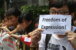 Students cover their mouths during an anti-Cybercrime Law protest in front of the Philippine Supreme Court in Manila. The Court declared constitutional several provisions in the Cybercrime Law including the one that penalizes online libel.