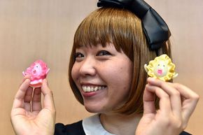 Japanese artist Megumi Igarashi shows small mascots shaped to represent vaginas, at a press conference after her first trial hearing in Tokyo. Igarashi  was arrested on obscenity charges for distributing 3D scans of her own genitals.