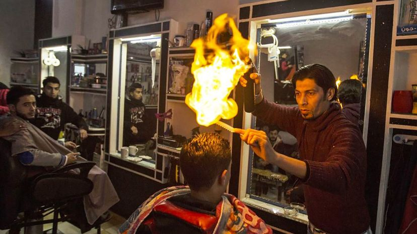 Ramadan Edwan, a Palestinian barber, uses fire in a hair-straightening technique with a client at his salon in the Rafah refugee camp, in the southern Gaza Strip on February 1, 2017. Mahmud Hams/AFP/Getty Images