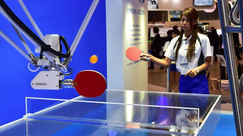 A demonstrator shows how Omron's FORPHEUS robot can train players in table tennis. Yoshikazu Tsuno/AFP/Getty Images