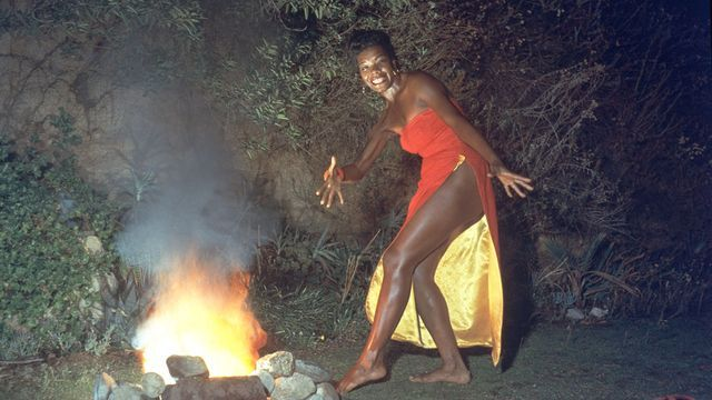 """Maya Angelou wears a red dress while dancing next to a fire in a promotional portrait taken for the cover of her album """"Miss Calypso."""""""
