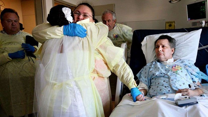 While holding her husband Johnny's hand, Robin Villalobos hugs their daughter Janette, who married her fiance Michael Arroyo at her father's bedside in the intensive care unit at Ronald Reagan UCLA Medical Center in 2009. Liz O. Baylen/Los Angeles Times via Getty Images