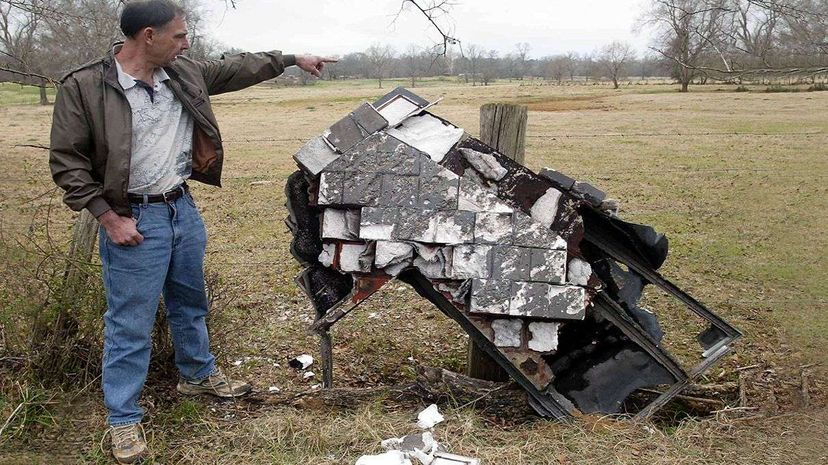 Texas resident Mac Powell points to a portion of the space shuttle Columbia that fell onto his ranch after the shuttle broke up in 2003. Mike Nelson/AFP/Getty Images