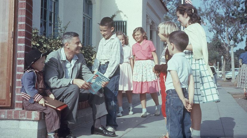 """Theodor Geisel, aka Dr. Seuss, holds his book """"The Cat in the Hat"""" as he talks to a group of children. Gene Lester/Getty Images"""