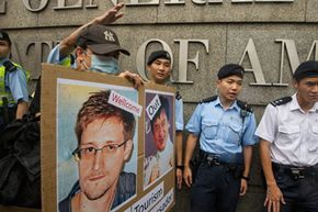 Hong Kong police officers stand guard outside the American Consulate in Hong Kong during a demonstration of support for Edward Snowden (pictured left on the sign) in June 2013.