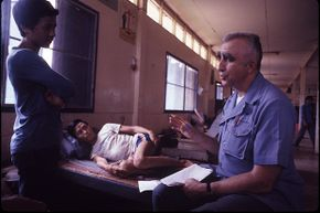 Dr. Amos Townsend, a retired US Air Force colonel interviews a Laotian victim of yellow rain at Ban Vinai Refugee Camp for Hmong people fleeing across the border to northeast Thailand, 1982.