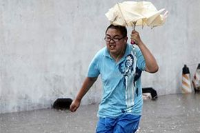 A man runs in a flooded street in Changsha, China in 2013. Floods and mudslides triggered by typhoon Utor killed 9 people in Hunan province.