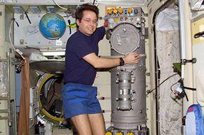 Astronaut Daniel W. Bursch, Expedition Four flight engineer, works on the Elektron Oxygen Generator in the Zvezda Service Module on the International Space Station (ISS).