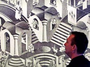 A man looks at artist M.C. Escher's artwork, displayed at the Escher Museum in The Hague, Netherlands.