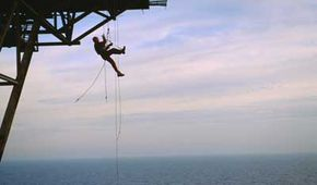 A remote access technician dangles underneath a North Atlantic oil rig to inspect the structure's underbelly.