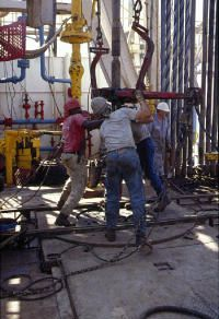 Rotary workers trip drill pipe.