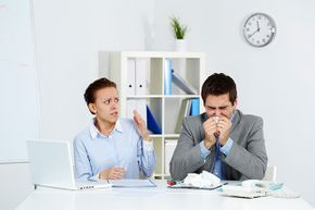 Use antibacterial wipes in your desk area when your coworker starts sneezing. And encourage him to go home.