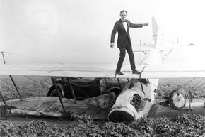 """Ormer Locklear walks on the wings of an airplane in a still from the 1920 silent film """"The Skywayman."""" Locklear later died while performing an aerial maneuver during nighttime shooting for the movie."""