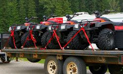 It's generally illegal (and unsafe) to ride an ATV on the street, so you'll have to tow it to the trail.