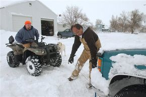 Two Colorado residents attempt to move a truck stuck in the ice using an ATV winch.