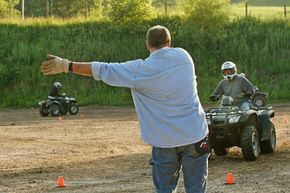 An ATV safety instructor guides students through a course in Burnsville, Minn. The class, offered by the national ATV Safety Institute, and funded by ATV manufacturers, offered $100 to ATV owners who completed it.