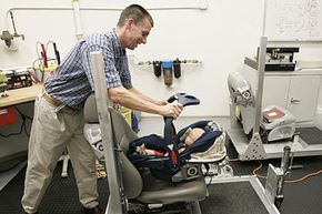 Takata technical manager Greg Stanley places an infant carrier on a seat for testing in Farmington Hills, Mich.