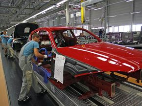 Workers fit the body of a BMW 1 in the BMW plant in Leipzig, Germany, in 2007.