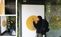 An unsuspecting but curious bystander takes a fake sneeze to the face at a bus shelter.
