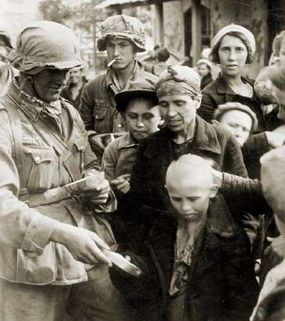 A Nazi German infantryman gives food to a malnourished Soviet child.