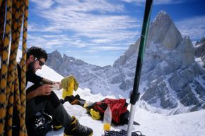 A climber rests below Aguja Standhardt, with the west face of Cerro Fitz Roy in the background, in Argentine Patagonia.