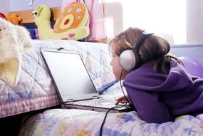 A young girl is intent on her computer game. Advergaming is often used in games targeted to children.