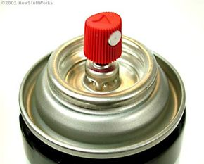 The plastic head on an aerosol can pushes down on a small valve, allowing the pressurized contents of the can to flow to the outside.