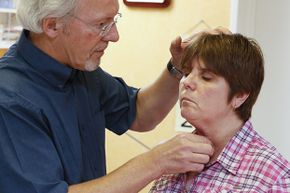 A doctor checks a woman's thyroid gland. Hypothyroidism can cause you to gain weight.