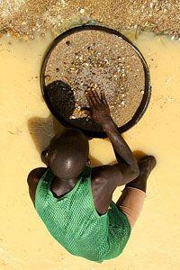 A diamond hunter pans for gems near Koidu, Sierra Leone