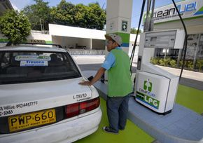 A gas station attendant fills up a taxi with liquefied petroleum gas. See pictures of alternative fuel vehicles.