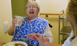 A nursing home resident gets help with her meal.