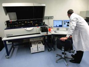 A researcher operates an LSR II, an advanced sample analyzing machine, at the opening of the Internaional AIDS Vaccine Initiative's new laboratory in New York City.
