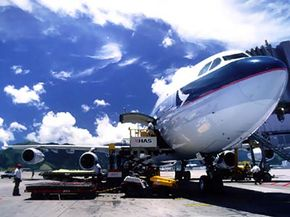Workers prepare to unload cargo from the lower hold of a jetliner.