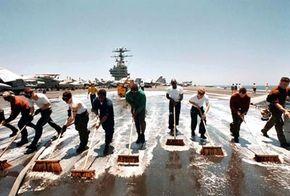Members of the USS George Washington crew scrub the flight deck.