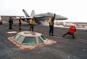 Steam rises from the catapult as an F/A-18C Hornet prepares to launch from the USS George Washington. You can see the catapult officer in the catapult control pod.