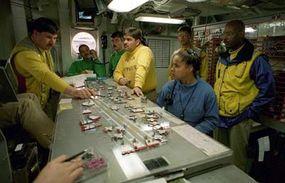 """Crew members on the USS George Washington circle around the """"Ouija Board."""""""