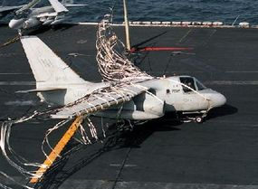 An S-3A Viking aircraft lands on the USS Abraham Lincoln with the help of the crash barricade. The plane had to make an unconventional landing due to a problem with its landing gear.