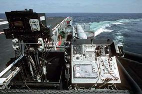 The video display console and communications/data board at the Landing Signals Officers' work station