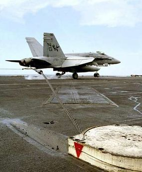 An F/A-18C Hornet catches an arresting wire on the USS Nimitz.
