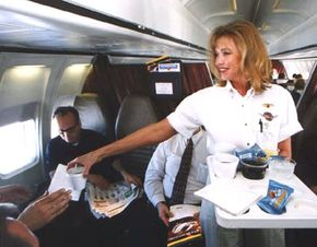"""A flight attendant serves a typical """"in-flight snack"""" consisting of drinks and peanuts."""