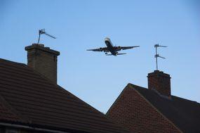 an airplane flies above a neighborhood